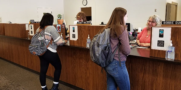 Two students talking to tellers in the student accounts building.
